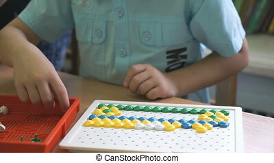 Preschool boy collects figure using colored chips -...