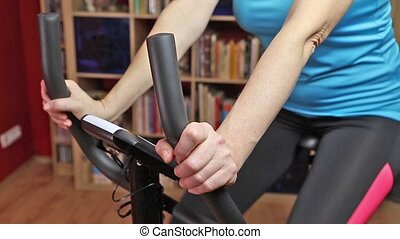 Woman cycling on bike trainer closeup - Middle age woman...