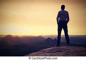 Tourist on cliff of  mountain summit. Outdoor activites.