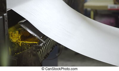 Long paper roll hanging, pulling from one part of equipment...