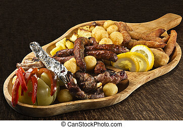 Rustic tray with various meats, cheese balls and assorted vegetables - isolated