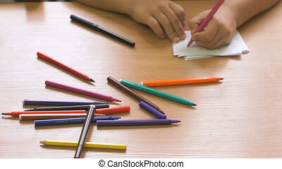 Little girl draws the picture using the felt pens