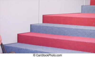 Businessman climbing up the stairs in office building.