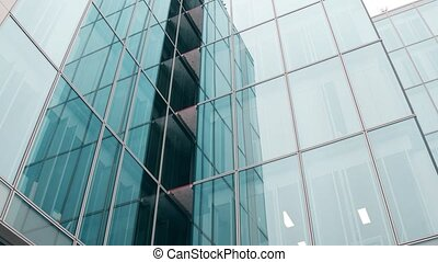 Close-up low angle steadicam shot of modern glass facade...