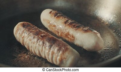Sausages cooking and sizzling in a frying pan. 4K