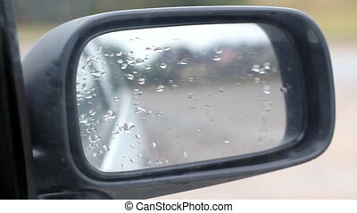 Car Side Mirror View With Water Rain Drops