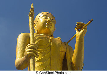 golden thai monk statue with blue sky