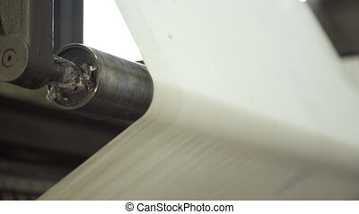 Long uncut clear paper on rolling machine in printing house....