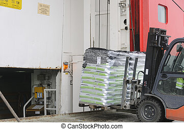 Fork lift loading goods on a ship