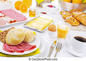 Table full with continental breakfast items, brightly lit -...