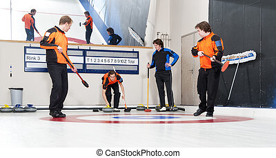 Curling players delivering stones during an end