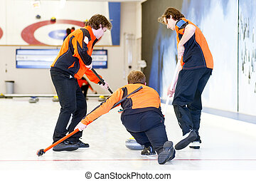 Curling team in action, delivering a stone to the house