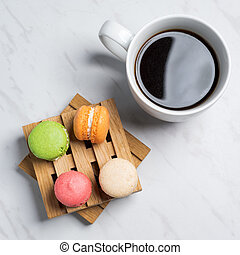 Sweet and colourful macaroons served on little wooden pallets with cup of coffee on a marble texture background. Traditional french dessert. Top view.