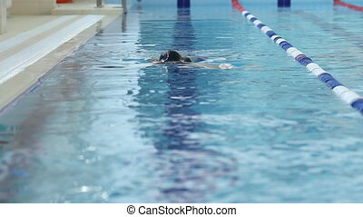 Young woman in goggles and cap swimming in the blue water indoor race pool.
