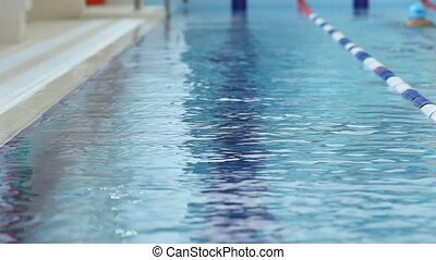 Young girl in goggles and cap swimming backstroke style in the blue water pool