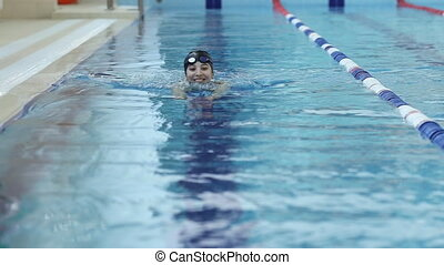 Young woman in goggles and cap swimming in the blue water indoor race pool