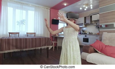 Young beautiful girl with virtual reality in modern interior...