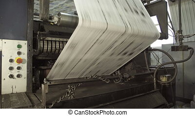 Long uncut paper on rolling machine in printing house.
