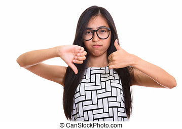 Young Asian teenage nerd girl giving thumbs up and down