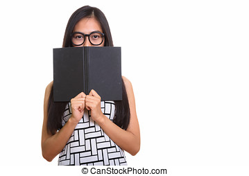 Young Asian teenage nerd girl hiding behind book
