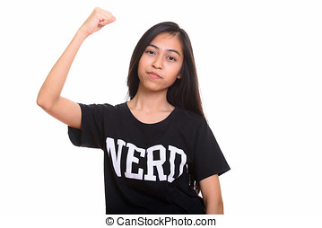 Studio shot of young Asian teenage nerd girl flexing arm
