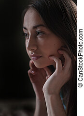 Portrait of a beautiful young woman looks out the window