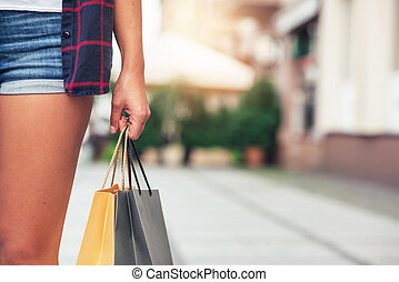 Young woman carrying shopping bags in the city - Closeup of...