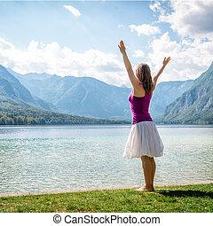 Woman meditating at the lake - serenity and yoga practicing...