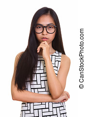 Studio shot of young Asian teenage nerd girl thinking