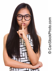 Young Asian teenage nerd girl with finger on lips