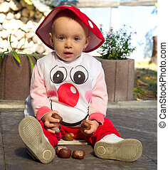 Baby girl dressed in a mushroom costume