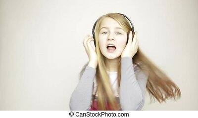 young girl listening music on headphones, singing and dancing