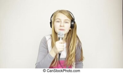 young girl listening music on headphones holding microphone,...
