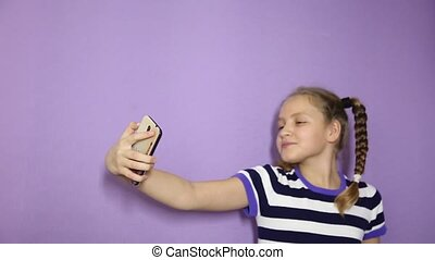 young girl with pigtails makes a selfie on a phone.
