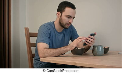 Young man using phone while eating breakfast. Professional...
