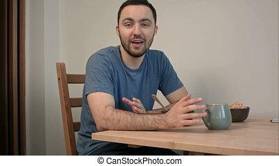Happy smiling man describing his breakfast to the camera....