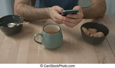 Man's hands holding phone at breakfast table