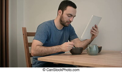 Young man reading news on tablet while eating breakfast....
