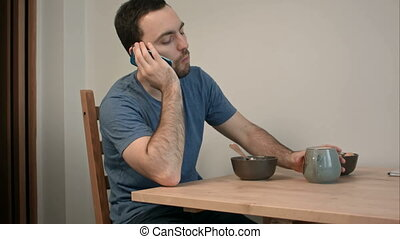 Young man having a phone call over breakfast