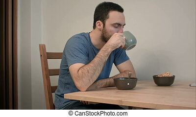 Sad and frustrated man drinking tea sitting at the kitchen table