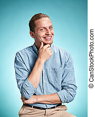 Happy excite young man smiling over blue background - Happy...