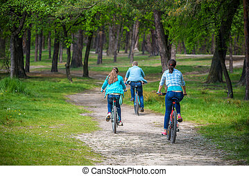 Parents With Daughter Riding Bikes In Park or summer forest. View from back, selective focus