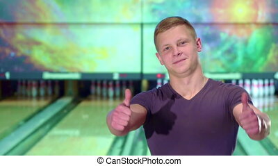 Man shows his thumbs up at the bowling alley - Young...