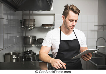 Chef in the kitchen reading on tablet