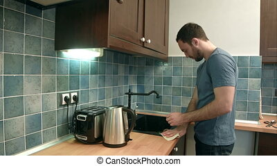 Young man cleaning the kitchen after washing dishes....