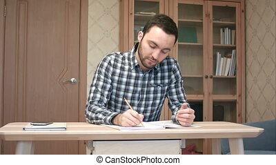 Happy student finishing writing his essay. Professional shot...