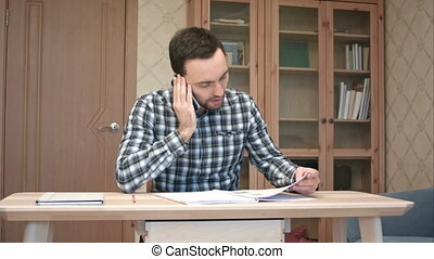 Young man talking on the phone while working at home....