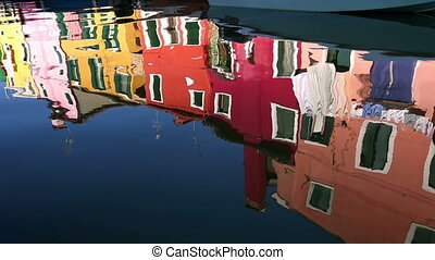 Reflection of a colorful houses in water canal, Burano...