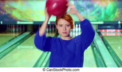 Girl spins with bowling ball in her hands - Pretty redhead...