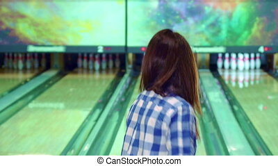 Girl knocks down pins at the bowling - Attractive brunette...